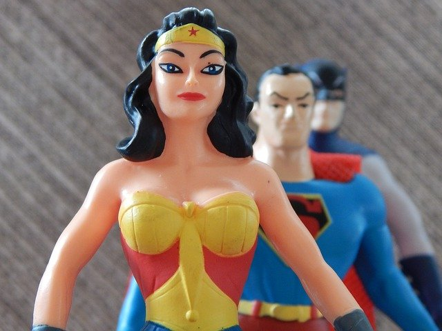 Wonder woman, superman, and batman toys lined up in confident power poses.