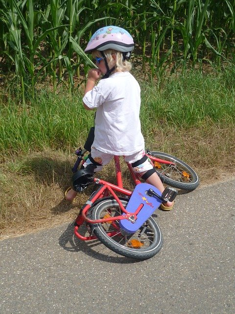 Child getting up with resilience after falling on his bike.