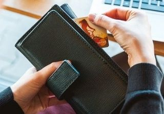 Credit Card being pulled from black leather wallet.