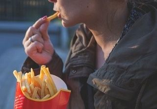 Woman in brown jacket eating golden French Fries.