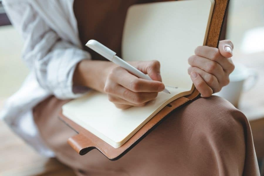 Woman writing positive self-talk phrases in leather bonded journal
