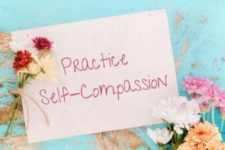 Practice Self-Compassion written on paper with 2 bouquets of flowers beside it