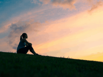 Woman sitting on grass practices self-compassion while gazing into sunset sky