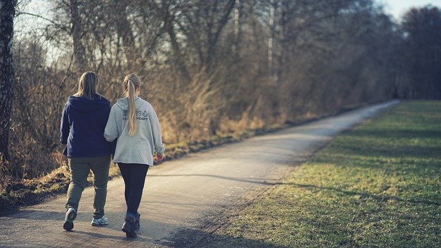 Mother and daughter walking on a paved path through park.