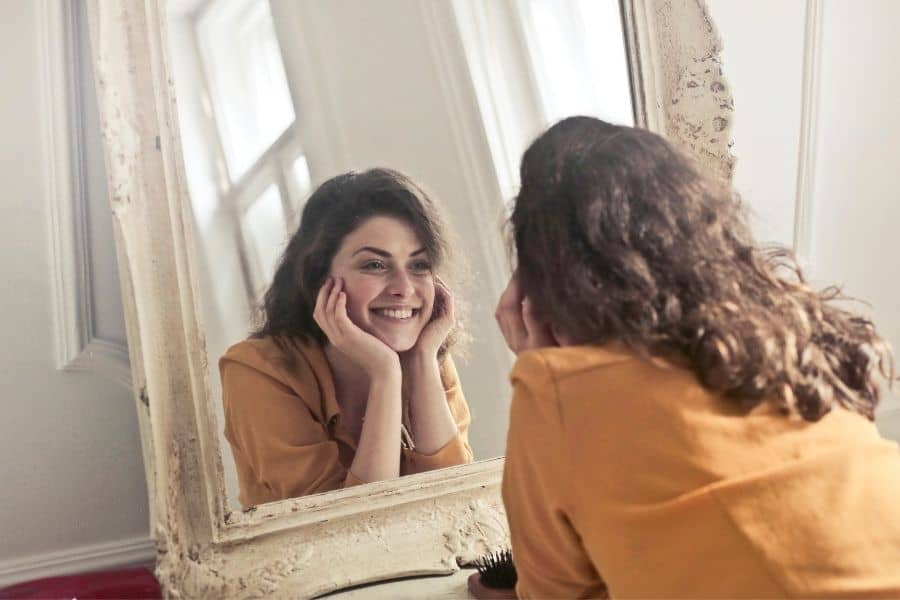 Young woman practicing positive self-talk with a mirror.