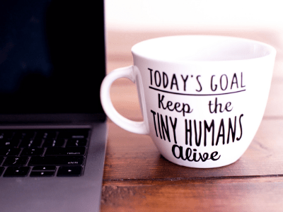 "Laptop and mug on table. Written on mug: ""Today's goal, keep the tiny humans alive."""