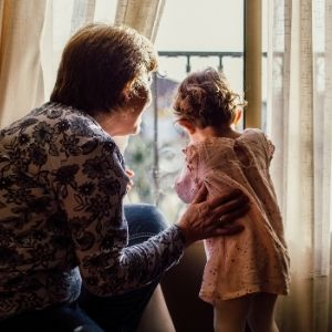 Grandmother and toddler grand daughter looking out window together.