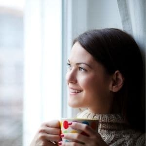 Smiling mom thinking positive thoughts holding a colorful mug near a sunny window.