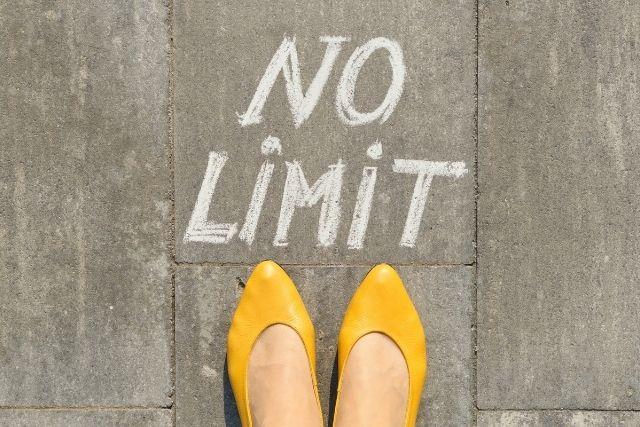 Yellow flats on sidewalk with chalk saying 'No Limit'
