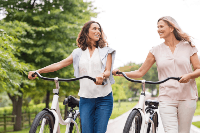 Stay-at-home mom walking bike outdoors along with a friend