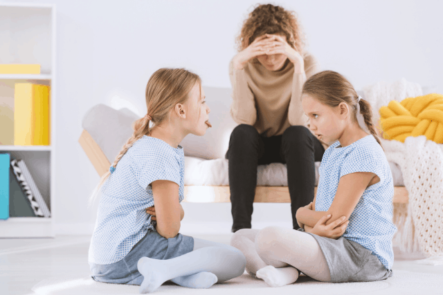 Overwhelmed stay-at-home mom as two children bicker at eachother.