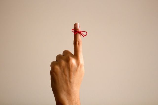 Female hand with red string tied around finger for a reminder to stay present.
