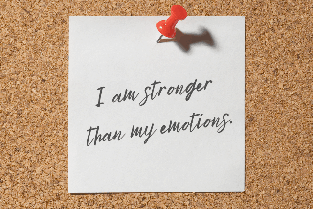 """Positive Affirmation: """"I am stronger than my emotions"""" written on a white post it tacked onto a cork board."""